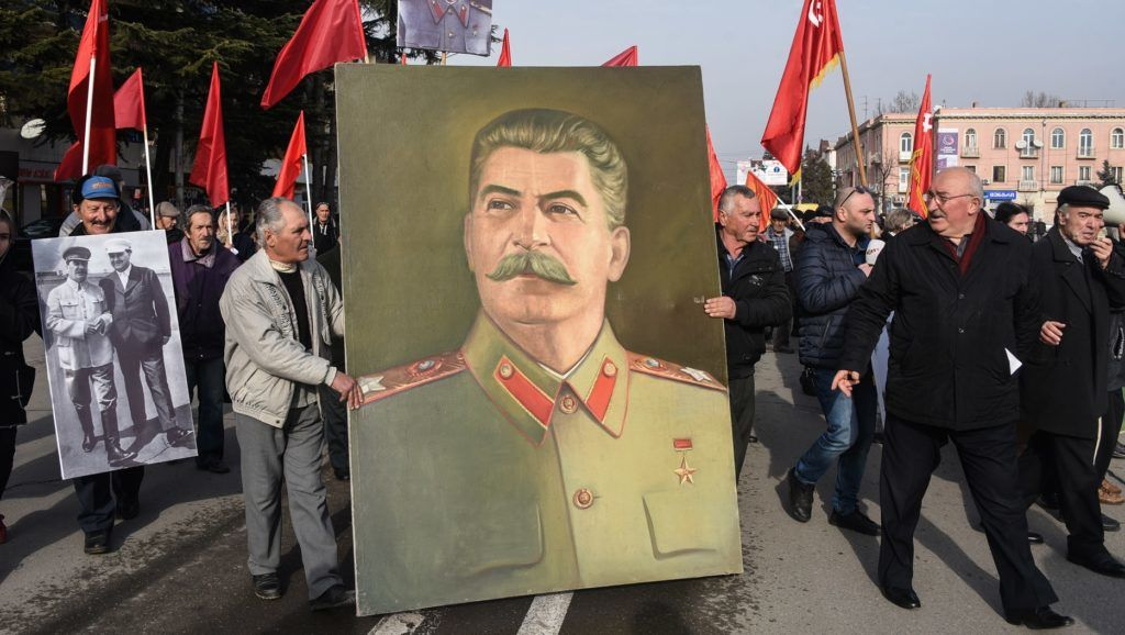 People carrying red flags and portraits of Soviet leader Joseph Stalin march during a ceremony marking the 138th anniversary of Stalin's birth, in Gori, on December 21, 2017. / AFP PHOTO / Vano SHLAMOV