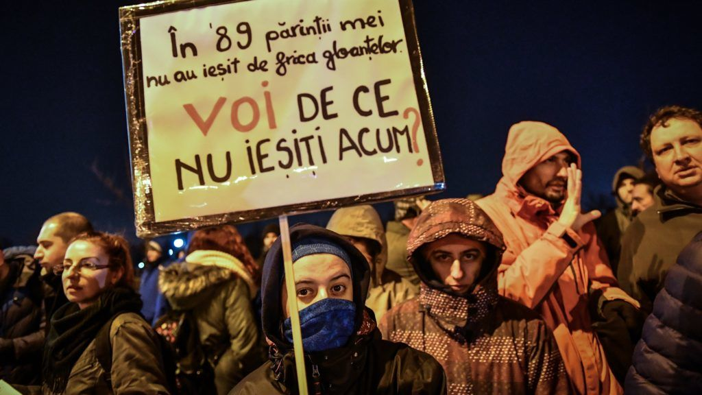 """A woman holds a placard reading """"In '89, my parents feard the bullets and didn't go out (on the streets to protest) / What is YOUR excuse today, not to go out (on the streets to protest) ?"""" during a protest next to the Parliament in Bucharest December 21, 2017. Romania's upper house approved judicial reforms that have sparked street protests and concerns abroad about the EU country's commitment to tackling corruption. Critics say that the changes will reduce the independence of magistrates and curb the powers of the DNA, the respected anti-corruption investigative body. Brussels worries that EU's second-poorest country is backtracking on tackling graft, and Washington has also expressed concerns. Thousands of Romanians including magistrates and law students have protested in recent weeks in Bucharest and other cities.  / AFP PHOTO / Daniel MIHAILESCU"""