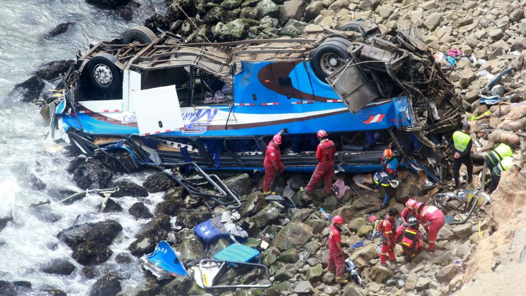 """Handout picture released by Peruvian agency Andina showing rescuers, police and firefighters working at the scene after a bus plunged around 100 meters (330 feet) over a cliff after colliding with a truck on a coastal highway near Pasamayo, around 45 km north of Lima, and killing at least 25 people on January 2, 2018. """"At least 25 people are dead and around five are injured among those found so far,"""" the head of the police's highway patrol division, Colonel Dino Escudero, said. The bus was travelling from Huacho, 130 km north of the capital, to Lima with 53 passengers on board. The spot where the accident occurred is known as the """"devil's curve.""""  / AFP PHOTO / ANDINA / HO / RESTRICTED TO EDITORIAL USE - MANDATORY CREDIT """"AFP PHOTO / ANDINA / HO"""" - NO MARKETING NO ADVERTISING CAMPAIGNS - DISTRIBUTED AS A SERVICE TO CLIENTS"""