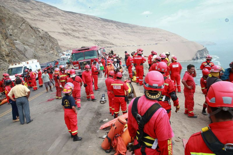 """Handout picture released by Peruvian agency Andina showing firefighters and rescuers working during rescue efforts after a bus plunged around 100 meters (330 feet) over a cliff after colliding with a truck on a coastal highway near Pasamayo, around 45 km north of Lima, and killing at least 25 people on January 2, 2018. """"At least 25 people are dead and around five are injured among those found so far,"""" the head of the police's highway patrol division, Colonel Dino Escudero, said. The bus was travelling from Huacho, 130 km north of the capital, to Lima with 53 passengers on board. The spot where the accident occurred is known as the """"devil's curve.""""  / AFP PHOTO / ANDINA / HO / RESTRICTED TO EDITORIAL USE - MANDATORY CREDIT """"AFP PHOTO / ANDINA / HO"""" - NO MARKETING NO ADVERTISING CAMPAIGNS - DISTRIBUTED AS A SERVICE TO CLIENTS"""