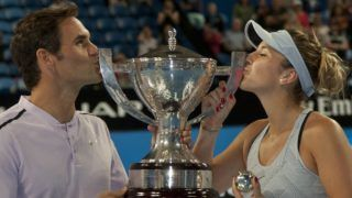 Roger Federer (L) and Belinda Bencic of Switzerland hoist the Hopman Cup after defeating Alexander Zverev and Angelique Kerber of Germany in the mixed doubles final on day eight of the Hopman Cup tennis tournament in Perth on January 6, 2018. / AFP PHOTO / TONY ASHBY / RESTRICTED TO EDITORIAL USE - STRICTLY NO COMMERCIAL USE
