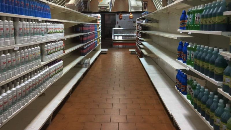 View of partially empty supermarket shelves in Caracas on January 6, 2018.  Venezuela's government forced more that 200 establishments to lower prices in the middle of a hyperinflationary spiral. / AFP PHOTO / JUAN BARRETO