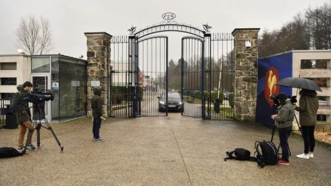 Reporters broadcast from the front entrance of the headquarters of the French Rugby Federation while a car drives through the gates on January 23, 2018 in Marcoussis, southwest of Paris, as police searches the premises as part of an investigation into suspicions of favouritism concerning the federation's president. The search at the federation's headquarters in Marcoussis, a southern suburb of Paris, was ordered by the public prosecutor in charge of financial cases. Federation president Bernard Laporte, whose lawyer said the home was also searched, is suspected of pressuring the FFR's appeals committee to reduce a sanction against Montpellier, owned by businessman Mohed Altrad, who owns the Altrad Group.  / AFP PHOTO / CHRISTOPHE SIMON