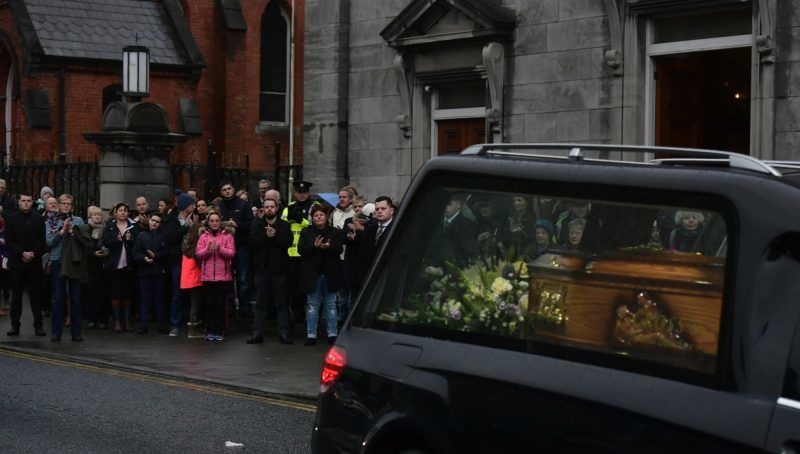 LIMERICK, IRELAND - JANUARY 21: Mourners and members of the public applaud the late Dolores O'Riordan as she leaves St. Joseph's church on January 21, 2018 in Limerick, Ireland. The Cranberries singer, aged 46 was found unresponsive in a London hotel on Monday. Police are not treating her death as suspicious. An inquest into O'Riordan's death was opened and adjourned until April while the coroner awaits test results. The Cranberries' debut album Everybody Else Is Doing It, So Why Can't We? sold 40 million records in the early 1990's. The funeral will take place in Ballybricken parish church on Tuesday. (Photo by Charles McQuillan/Getty Images)