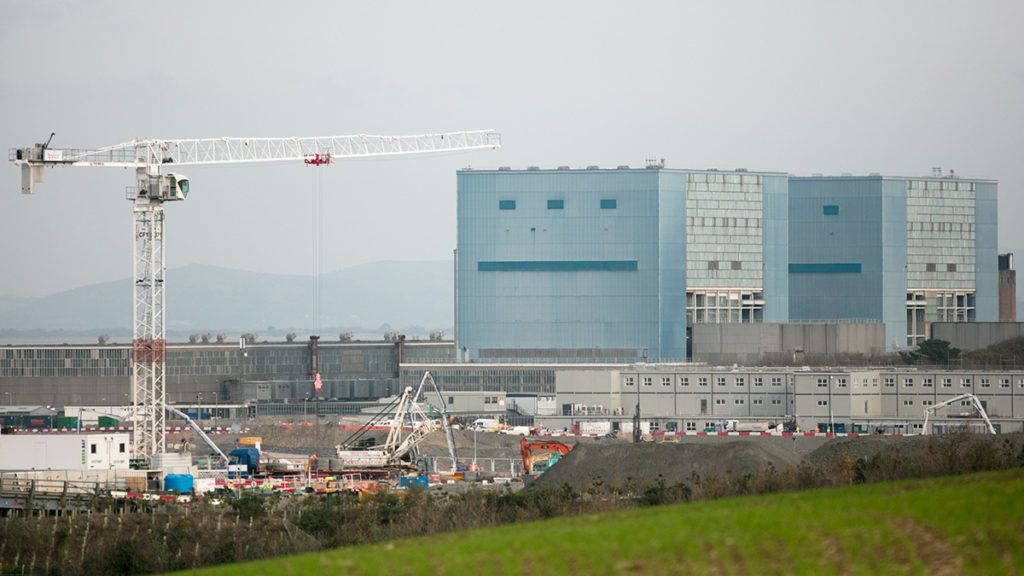 BRIDGWATER, ENGLAND - NOVEMBER 01:  A tower cranes operates in front of the Hinkley A buildings at the construction site of the Hinkley Point C nuclear power station being constructed near Bridgwater on November 1, 2017 in Somerset, England. Since the go-ahead to construct the Hinkley Point C nuclear power station by EDF Energy, was given in October 2016 it has become one of the largest construction sites in Europe with around 2,000 workers on site every day. The two new reactors, Britain's first power plant in 20 years and being built adjacent to the existing Hinkley Point A and B nuclear power stations next to the Bristol channel, are planned to be switched on in the middle of the next decade and is hoped will provide 7percent of the UK's electricity. In July, EDF announced its total cost was likely to rise by £1.5bn to £19.6bn and could be delayed by up to 15 months.  (Photo by Matt Cardy/Getty Images)