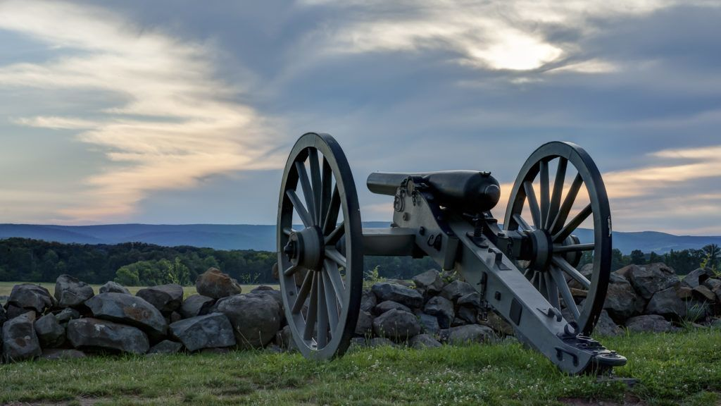 Civil War cannon & carriage behind stone wall against darkening blue skies with white clouds.