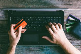 Man Hands holding credit card and using laptop in the evening. Online shopping, online banking and online marketing. shallow depth of field, toning photo