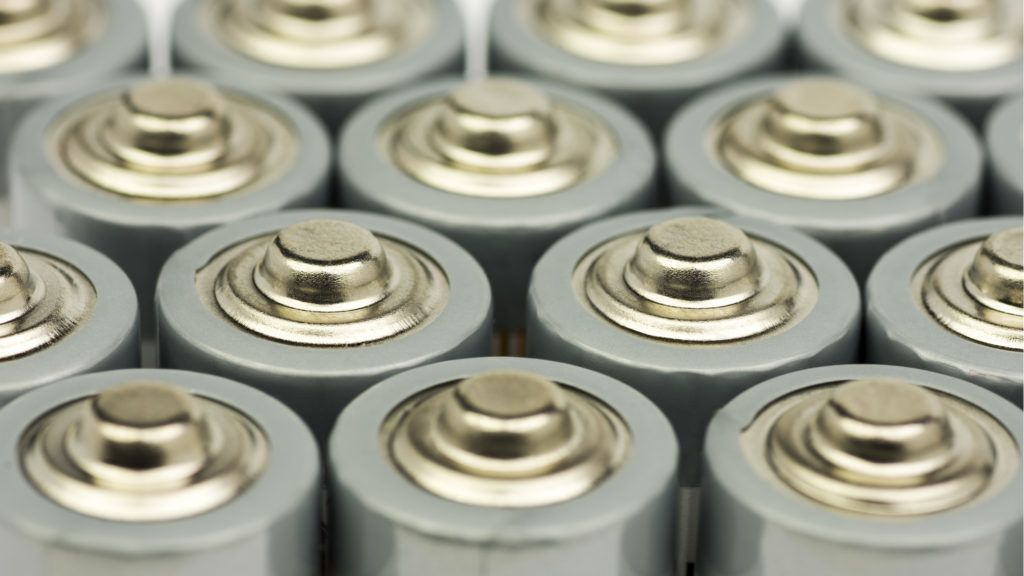 Multiple rows of standing AA batteries with blurred backgrounds