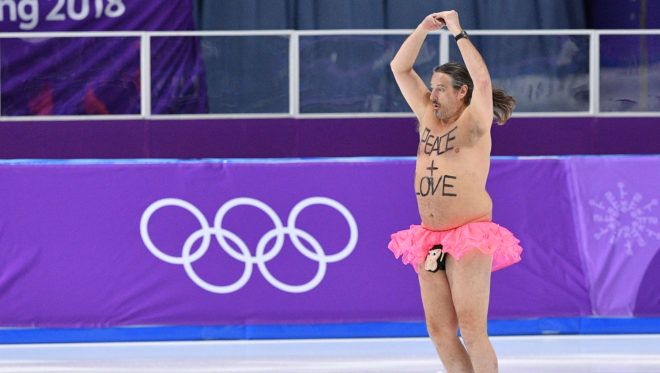 A shirtless man clad in a tutu dances on the rink following the men's 1,000m speed skating event medal ceremony during the Pyeongchang 2018 Winter Olympic Games at the Gangneung Oval in Gangneung on February 23, 2018. / AFP PHOTO / Mladen ANTONOV