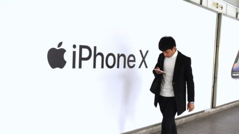--FILE--A Chinese pedestrian walks past an advertisement of iPhone X smartphone in Shanghai, China, 7 December 2017.