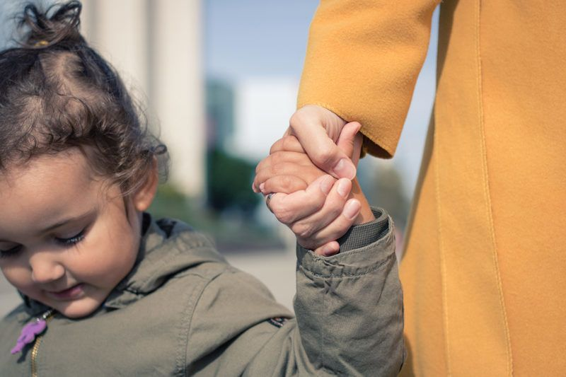 Close up of little girl holding hands with her mother. Mother and daughter bonds.