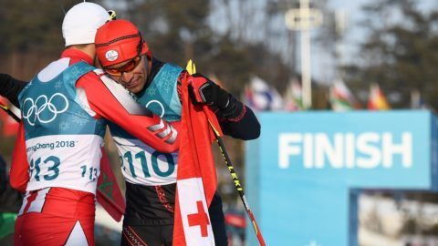 Morocco's Samir Azzimani (L) congratulates Tonga's Pita Taufatofua after he crossed the finish line during the men's 15km cross country freestyle at the Alpensia cross country ski centre during the Pyeongchang 2018 Winter Olympic Games on February 16, 2018 in Pyeongchang.  / AFP PHOTO / FRANCK FIFE