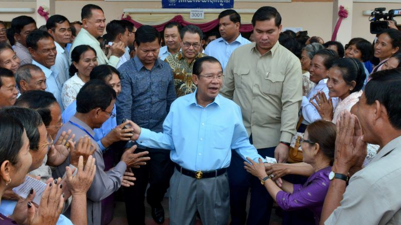 """Cambodia's Prime Minister Hun Sen (C) greets commune councillors at a polling station in Kandal province on February 25, 2018. Voting for Cambodia's Senate began on February 25 in an election decried by critics as a """"farce"""", with Prime Minister Hun Sen's ruling party set to dominate months after the country's only viable opposition party was dissolved. / AFP PHOTO / Khem SOVANNARA"""