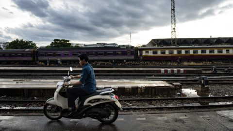 This picture taken on September 1, 2016 shows a man driving a scooter along a platform next to railway tracks at Hua Luampong central train station in Bangkok. / AFP PHOTO / LILLIAN SUWANRUMPHA