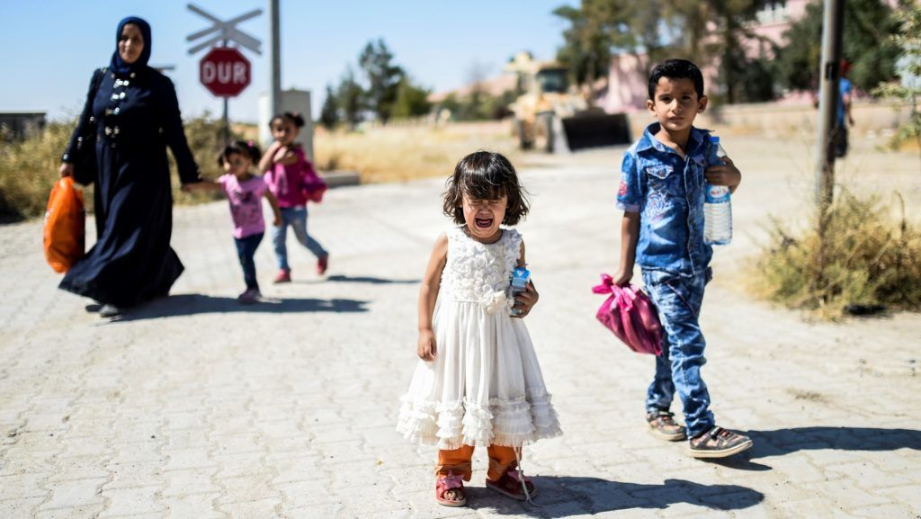 Syrian refugees walk on their way back to the Syrian city of Jarabulus  on September 7, 2016 at Karkamis crossing gate, in the southern region of Kilis. / AFP PHOTO / BULENT KILIC