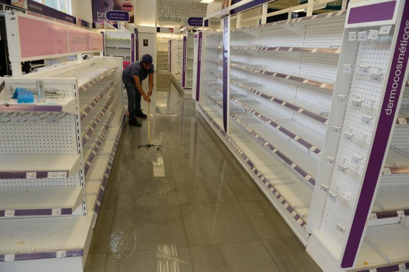 Employees clean the aisles in a looted pharmacy in Maracay, Aragua state, Venezuela on June 27, 2017. / AFP PHOTO / FEDERICO PARRA