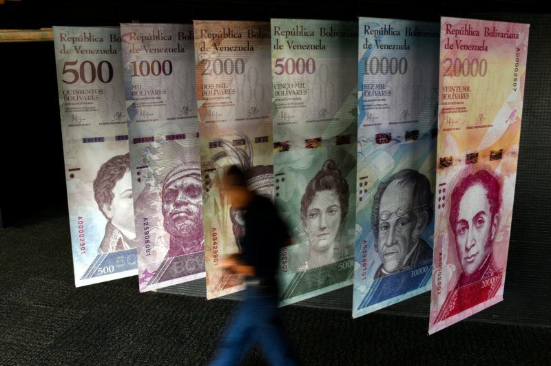 """A man walks past banners showing banners depicting Venezuela's currency, the Bolivar, at the Central Bank of Venezuela (BCV) in Caracas on January 31, 2018. Venezuelan President Nicolas Maduro signed the proposal of a new digital currency called """"Petro"""" to try to combat the economic crisis. / AFP PHOTO / FEDERICO PARRA"""