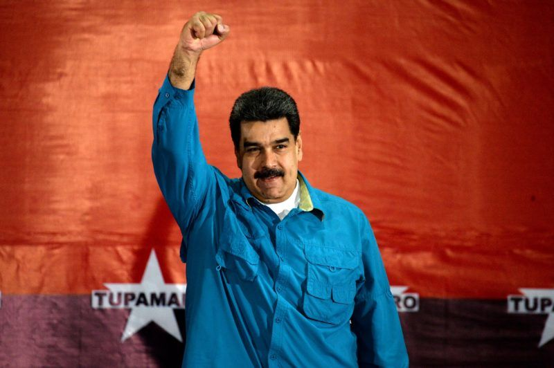 """Venezuelan President Nicolas Maduro raises his fist during a rally in Caracas on February 3, 2018. Venezuelan President Nicolas Maduro urged the electoral authorities and the Constituent Assembly Saturday to announce the date of the upcoming presidential elections by Monday """"at the latest.""""  / AFP PHOTO / FEDERICO PARRA"""