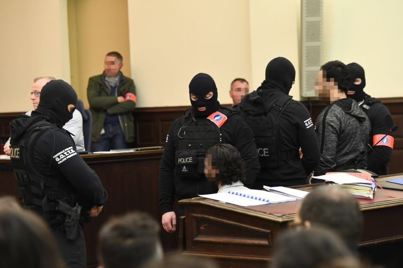 """Prime suspect in the November 2015 Paris attacks Salah Abdeslam (L) sits beside his alleged accomplice Sofiane Ayari (R) as they are surrounded by Belgian special police officers in the courtroom at the """"Palais de Justice"""" courthouse in Brussels for the opening of his trial, on February 5, 2018. The trial opens on February 5, 2018 of Paris attacks suspect Salah Abdeslam and his alleged accomplice Sofiane Ayari, over a shootout in Brussels that led to their capture. / AFP PHOTO / Emmanuel DUNAND"""