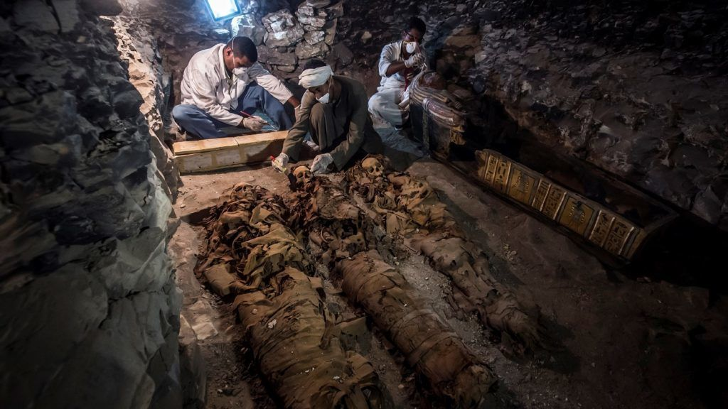 """A picture taken on September 9, 2017 shows Egyptian labourers and archaeologists unearthing mummies at a newly-uncovered ancient tomb for a goldsmith dedicated to the ancient Egyptian god Amun, in the Draa Abul Naga necropolis on the west bank of the ancient city of Luxor, which boasts ancient Egyptian temples and burial grounds. The finds at the tomb of """"Amun's Goldsmith, Amenemhat"""", which dates back to the New Kingdom (16th to 11th centuries BC), also contained a sculpture carved into a recess of him seated beside his wife, with a portrait of their son painted between them, in addition to another 150 small funerary statues carved in wood, clay and limestone. A burial shaft in the tomb led to a chamber where the archaeologists discovered mummies, funerary statues and masks, the antiquities ministry said. / AFP PHOTO / KHALED DESOUKI"""