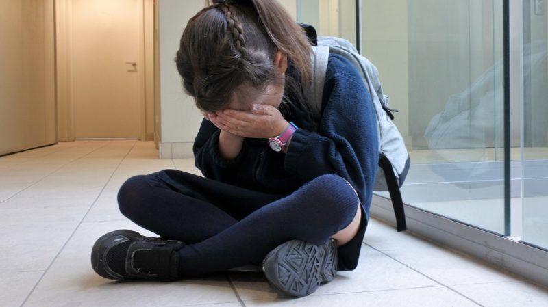 One young elementary school girl (age 7)  wearing school uniform and backpack sitting on a corridor floor crying. Childhood and education concept. copy space