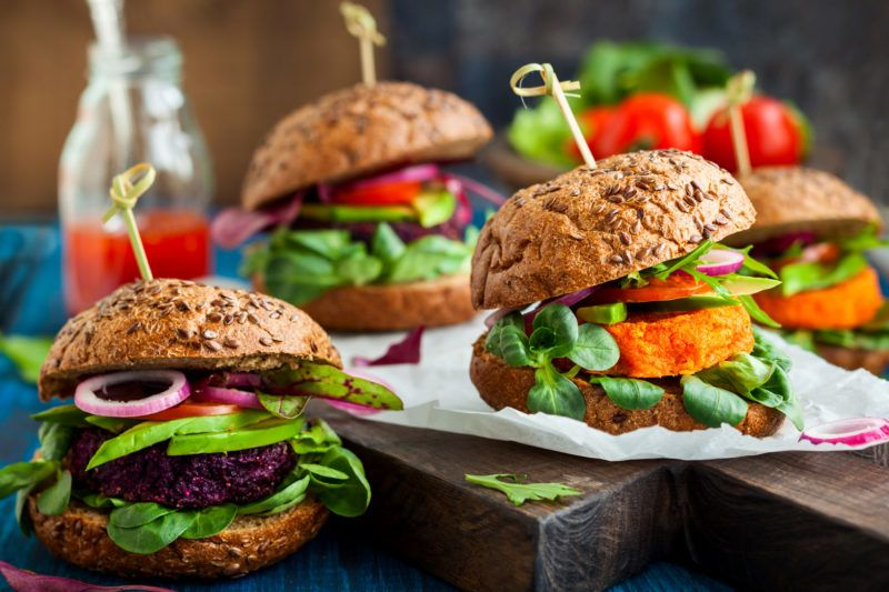Veggie beet and carrot burgers with avocado on the vintage wooden board