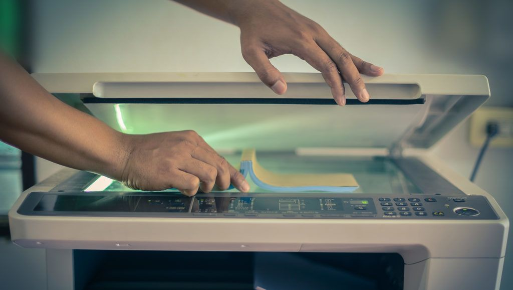 The hands placing a book for photocopying