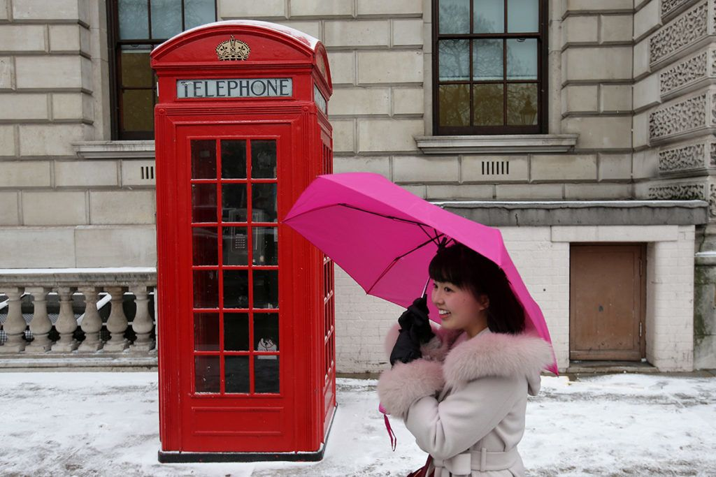 A tourist walks past a phone box as snow covers the streets on March 1, 2018 in London.Fresh heavy snowfalls and icy blizzards were expected to lash Europe Thursday as the region shivers in a deadly deep-freeze that has gripped countries from the far north to the Mediterranean south.     / AFP PHOTO / Daniel LEAL-OLIVAS
