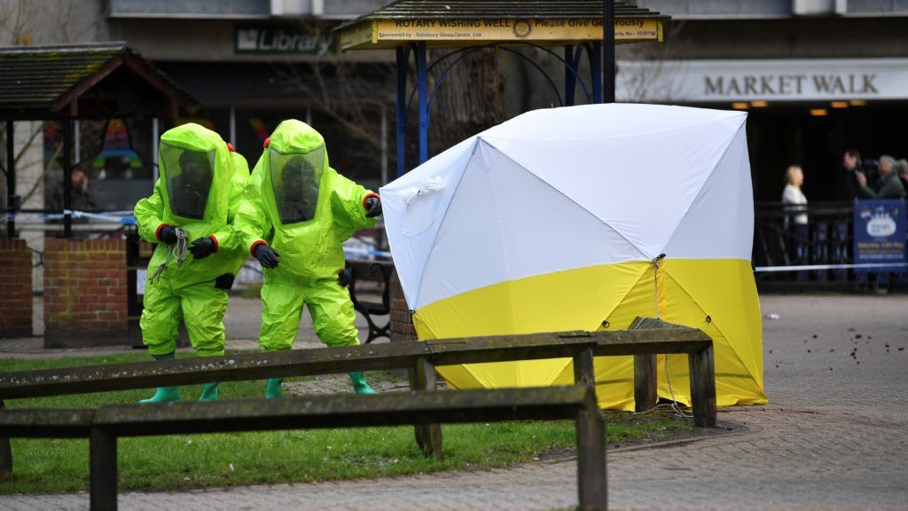 """Members of the emergency services in green biohazard encapsulated suits afix the tent over the bench where a man and a woman were found on March 4 in critical condition at The Maltings shopping centre in Salisbury, southern England, on March 8, 2018 after the tent became detached.  British detectives on March 8 scrambled to find the source of the nerve agent used in the """"brazen and reckless"""" attempted murder of a Russian former double-agent and his daughter. Sergei Skripal, 66, who moved to Britain in a 2010 spy swap, is unconscious in a critical but stable condition in hospital along with his daughter Yulia after they collapsed on a bench outside a shopping centre on Sunday.  / AFP PHOTO / Ben STANSALL"""