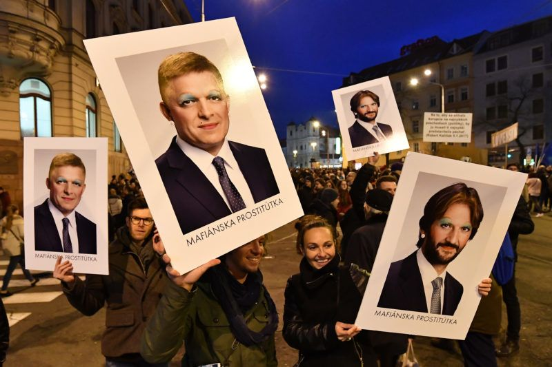 """Protesters holds placards bearing faceted portraits of Slovakia's Prime Minister Robert Fico (L) and Interior Minister Robert Kalinak (R) during a rally under the slogan """"For a Decent Slovakia"""", against corruption and to pay tribute to murdered Slovak journalist Jan Kuciak and his fiancee Martina Kusnirova on March 9, 2018 at the Slovak National Uprising (SNP) square in Bratislava, Slovakia. Demonstrations were expected to be held in dozens of Slovak cities and also abroad after the murder of investigative journalist Jan Kuciak, who was probing alleged high-level political corruption  / AFP PHOTO / JOE KLAMAR"""