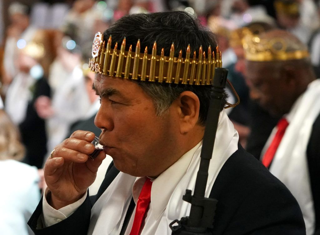 """A man wearing a crown of rifle shells, takes communion, as worshippers at World Peace and Unification Sanctuary attend services February 28, 2018 in New Foundland, Pennsylvania.Hundreds of worshipers gathered inside a Pennsylvania-based church at a blessing ceremony for couples featuring their AR-15 rifles. World Peace and Unification Sanctuary in Newfoundland believes the AR-15 symbolizes the """"rod of iron"""" in the biblical book of Revelation, and encouraged couples to bring the weapons to the commitment ceremony. / AFP PHOTO / Don EMMERT"""