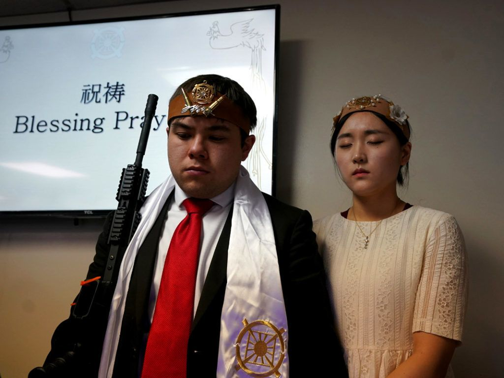 """Worshippers at World Peace and Unification Sanctuary hold weapons during their service February 28, 2018 in Newfoundland, Pennsylvania.Hundreds of worshipers gathered inside a Pennsylvania-based church at a blessing ceremony for couples featuring their AR-15 rifles. World Peace and Unification Sanctuary in Newfoundland believes the AR-15 symbolizes the """"rod of iron"""" in the biblical book of Revelation, and encouraged couples to bring the weapons to the commitment ceremony. / AFP PHOTO / Don EMMERT"""