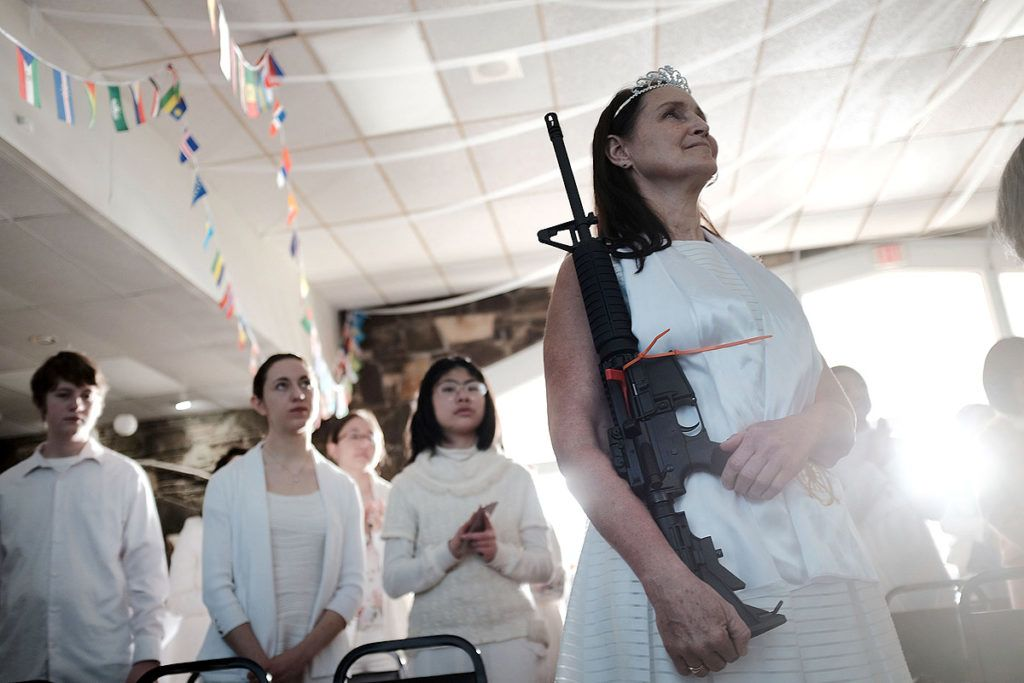 """NEWFOUNDLAND, PA - FEBRUARY 28: A woman holds an AR-15 rifle during a ceremony at the World Peace and Unification Sanctuary in Newfoundland, Pennsylvania on February 28, 2018 in Newfoundland, Pennsylvania. The controversial church, which is led by the son of the late Rev. Sun Myung Moon, believes the AR-15 symbolizes the """"rod of iron"""" in the biblical book of Revelation, and it has encouraged couples to bring the weapons to a """"commitment ceremony"""" or """"Perfection Stage Book of Life Registration Blessing"""". Officials in the rural area in the Pocono Mountains have reportedly told elementary school parents that their children will be relocated on Wednesday to accommodate the AR-15 ceremony. The semiautomatic rifles are similar to the weapons used in a Florida high school shooting two weeks earlier.   Spencer Platt/Getty Images/AFP"""