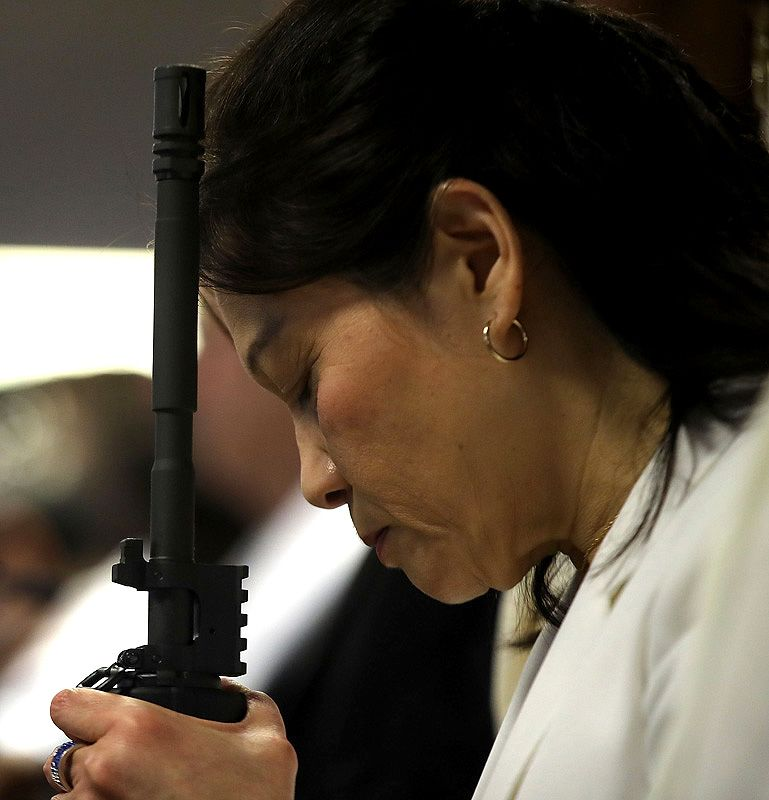 """NEWFOUNDLAND, PA - FEBRUARY 28: A woman prays while holding an AR-15 rifle during a ceremony at the World Peace and Unification Sanctuary in Newfoundland, Pennsylvania on February 28, 2018 in Newfoundland, Pennsylvania. The controversial church, which is led by the son of the late Rev. Sun Myung Moon, believes the AR-15 symbolizes the """"rod of iron"""" in the biblical book of Revelation, and it has encouraged couples to bring the weapons to a """"commitment ceremony"""" or """"Perfection Stage Book of Life Registration Blessing"""". Officials in the rural area in the Pocono Mountains have reportedly told elementary school parents that their children will be relocated on Wednesday to accommodate the AR-15 ceremony. The semiautomatic rifles are similar to the weapons used in a Florida high school shooting two weeks earlier.   Spencer Platt/Getty Images/AFP"""