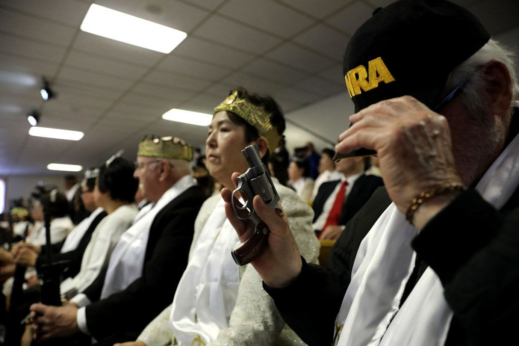 """NEWFOUNDLAND, PA - FEBRUARY 28: A man holds a pistol during a ceremony at the World Peace and Unification Sanctuary in Newfoundland, Pennsylvania on February 28, 2018 in Newfoundland, Pennsylvania. The controversial church, which is led by the son of the late Rev. Sun Myung Moon, believes the AR-15 symbolizes the """"rod of iron"""" in the biblical book of Revelation, and it has encouraged couples to bring the weapons to a """"commitment ceremony"""" or """"Perfection Stage Book of Life Registration Blessing"""". Officials in the rural area in the Pocono Mountains have reportedly told elementary school parents that their children will be relocated on Wednesday to accommodate the AR-15 ceremony. The semiautomatic rifles are similar to the weapons used in a Florida high school shooting two weeks earlier.   Spencer Platt/Getty Images/AFP"""