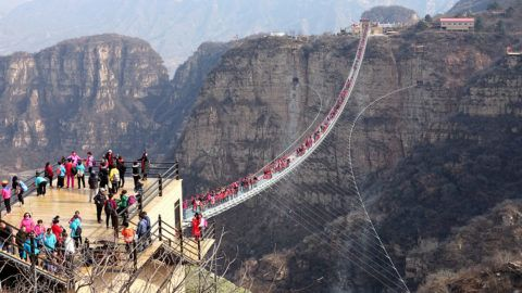 Tourists throng to walk on the world's longest glass bridge in the Hongyagu Scenic Area in Pingshan county, Shijiazhuang city, north China's Hebei province, 20 March 2018.