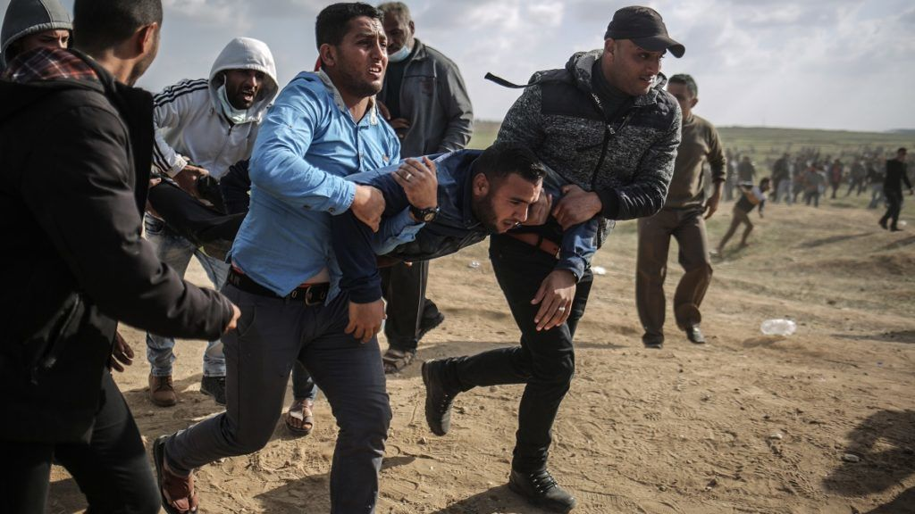 """GAZA CITY, GAZA - MARCH 30: A wounded Palestinian demonstrator is being moved away from the site after the intervention of Israeli security forces during the """"Great March of Return"""" at Ez-Zeitoun town south of Gaza City, Gaza on March 30, 2018. Dubbed the """"Great Return March"""", Friday's rallies in the Gaza Strip also coincide with Land Day, which commemorates the murder of six Palestinians by Israeli forces in 1976. It is also intended to pressure Israel to lift its decade-long blockade of the coastal enclave.  Ali Jadallah / Anadolu Agency"""