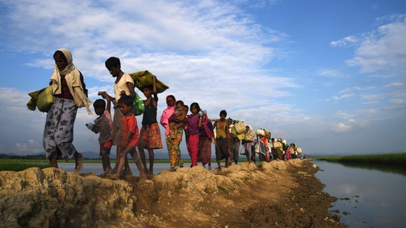 (FILES) In this file photo taken on November 2, 2017, Rohingya Muslim refugees who were stranded after leaving Myanmar walk towards the Balukhali refugee camp after crossing the border in Bangladesh's Ukhia district. Buddhism may be touted in the west as an inherently peaceful philosophy but a surge in violent rhetoric from small but increasingly influential groups of hardline monks in parts of Asia is upending the religion's tolerant image. In Myanmar, ultra-nationalist monks led by firebrand preacher Ashin Wirathu have poured vitriol on the country's small Muslim population, cheering a military crackdown forcing nearly 700,000 Rohingya Muslim into Bangladesh. / AFP PHOTO / Dibyangshu SARKAR
