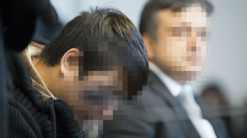 Hussein K (L), who is accused of raping and killing a young woman in October 2016, waits at a court room prior to the expected proclamation of sentence at the regional court in Freiburg, southern Germany, on March 22, 2018. The asylum seeker claiming to be from Afghanistan faces his verdict for the rape and murder of a student that fuelled a backlash against a mass migrant influx. / AFP PHOTO / THOMAS KIENZLE / GERMAN COURT REQUESTS THAT THE FACES OF THE DEFENDANT AND OF JUDICIAL OFFICERS  MUST BE MADE UNRECOGNISABLES