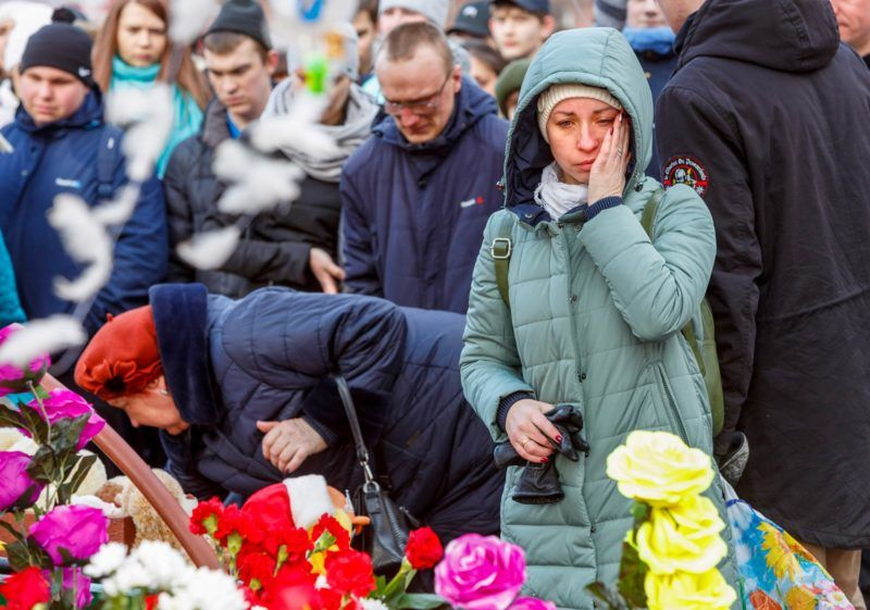 A woman dries her tears as people lay flowers in tribute to the victims of the fire at the shopping centre in Kemerovo on March 26, 2018. At least 53 bodies have been recovered from a fire that swept through a busy shopping centre in an industrial city in Siberia, Russian news agencies said Monday. Many people are also still missing from the blaze that broke out Sunday in the city of Kemerovo, the agencies quoted emergency services as saying. A previous toll put the number of dead at 37 with nearly 70 missing, including 40 children.   / AFP PHOTO / Kommersant Photo / Sergei GAVRILENKO / RUSSIA OUT