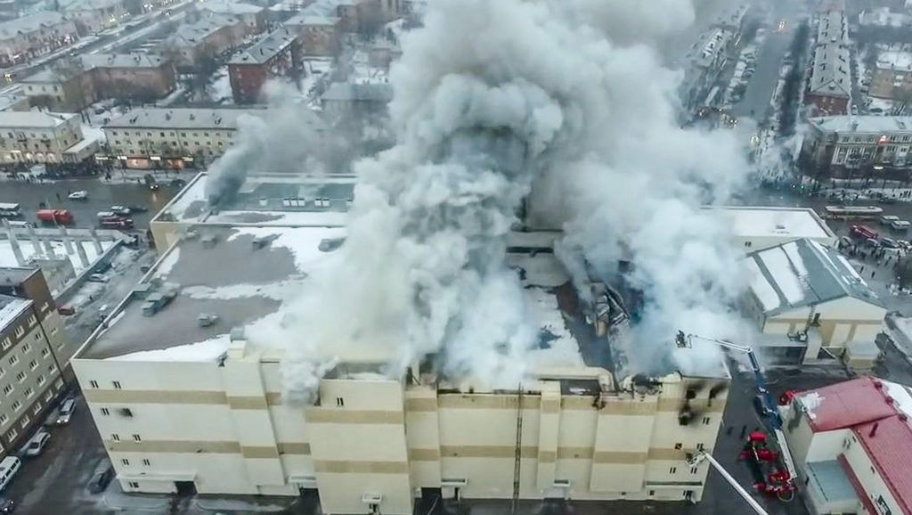 An aerial view taken on March 25, 2018 with a drone shows a fire of the shopping centre in Kemerovo. A total of 64 people, many of them children, perished in a fire that ravaged a busy shopping mall in an industrial city in Siberia, officials said on March 26, 2018 as rescuers searched through piles of charred rubble to recover bodies. Russian television showed images of thick black smoke pouring out of the roof of the Winter Cherry shopping centre in the city of Kemerovo, which also houses a sauna, a bowling alley and a multiplex cinema and was packed with people on Sunday afternoon.    / AFP PHOTO / STR