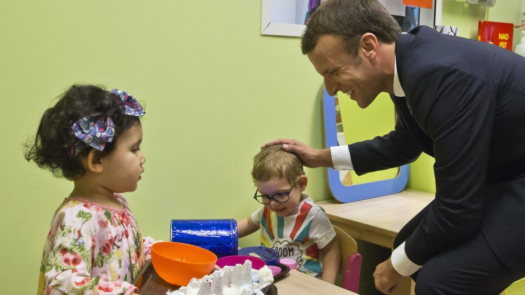 French President Emmanuel Macron (R) visits a nursery school, in Gennevilliers, north of Paris, on October 17, 2017, as part of his action to combat children and youth poverty. / AFP PHOTO / POOL / Michel Euler