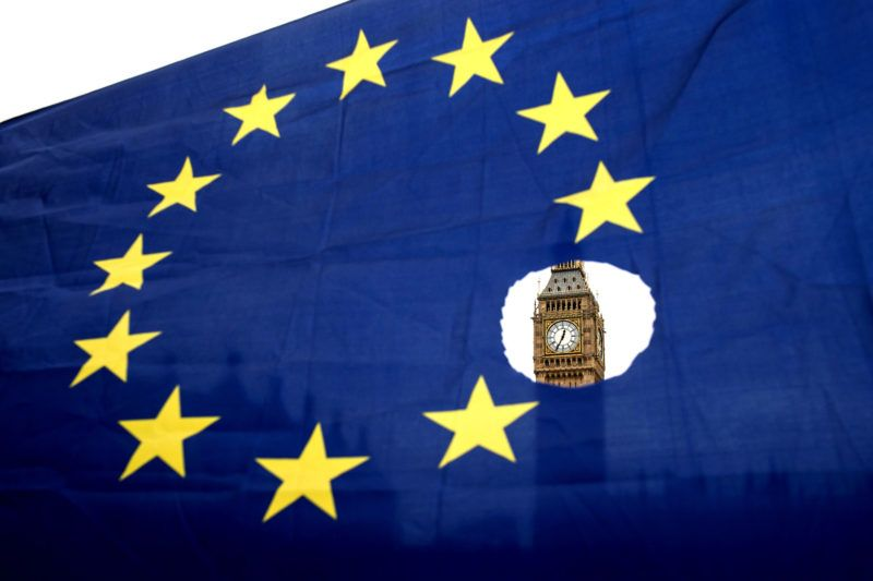 (FILES) In this file photo taken on March 29, 2017 a pro-remain protester holds up an EU flag with one of the stars symbolically cut out in front of the Houses of Parliament shortly after British Prime Minister Theresa May announced to the House of Commons that Article 50 had been triggered in London. Britain is set to leave the EU on March 29, 2019, almost three years after the referendum vote for Brexit, having triggered the two-year Article 50 withdrawal process in 2017, and negotiations on the future partnership are meant to be wrapped up by October. / AFP PHOTO / OLI SCARFF