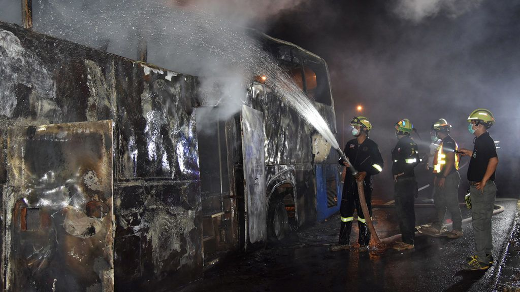 """This photo by Dailynews taken in the early hours of March 30, 2018 shows firefighters extinguishing a bus fire, in which at least 20 Myanmar migrant workers died, in the Thai western border province of Tak. Twenty Myanmar migrant workers died early on March 30 as fire tore through a bus taking them from a Thai border town to Bangkok, officials said. / AFP PHOTO / DAILYNEWS / Thailand OUT / RESTRICTED TO EDITORIAL USE - MANDATORY CREDIT """"AFP/DAILYNEWS"""""""