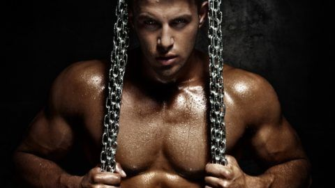 Handsome young man posing with metal chain. Perfect body.