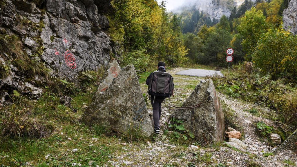 """A picture taken on October 4, 2016 shows a cameraman walking through the concrete obstacles in the disputed Kosovo-Montenegro border in the village of Cakor, western Kosovo. There are no guards in the uninhabited Rugova mountains bordering Montenegro, only sheep on pasture land, but a dispute over defining the borderline could push Kosovo into chaos as the political opposition views the demarcation deal as close to """"treason"""". The tiny Balkan territory, which unilaterally proclaimed independence from Serbia in 2008, last year reached a border demarcation agreement with its western neighbour, but Kosovo's parliament has yet to ratify it. / AFP PHOTO / ARMEND NIMANI"""