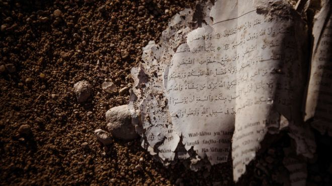 Pages of a Kur'an (Koran) as found abandoned on the ground.