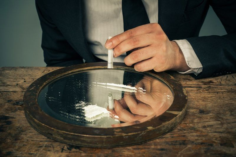 Young businessman is snorting cocaine with a rolled up banknote