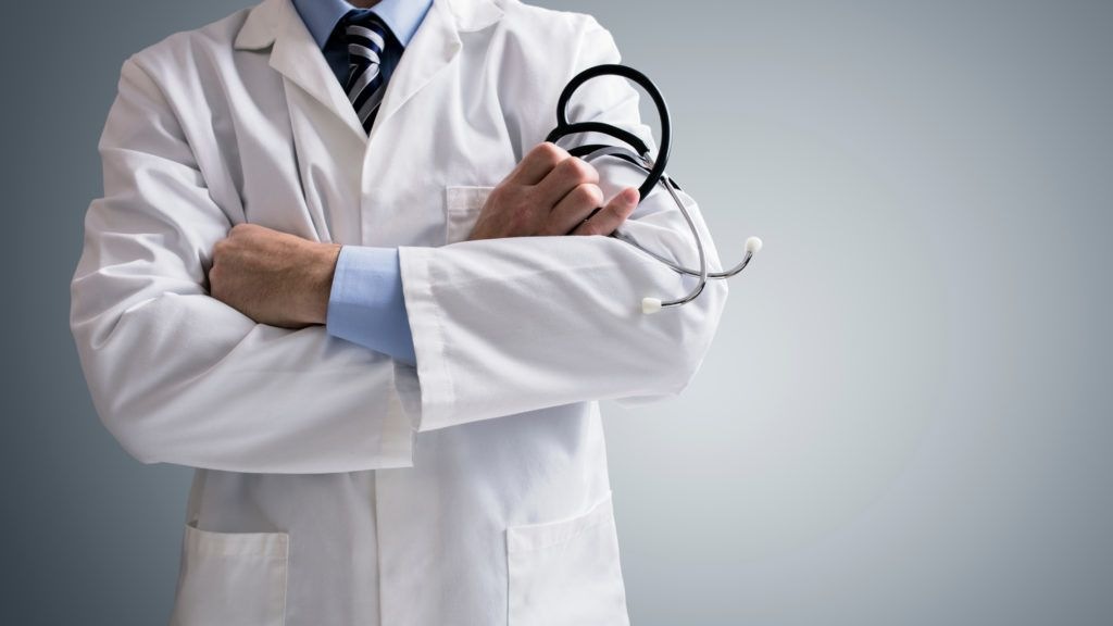 Doctor holding a stethoscope with arms crossed and copy space