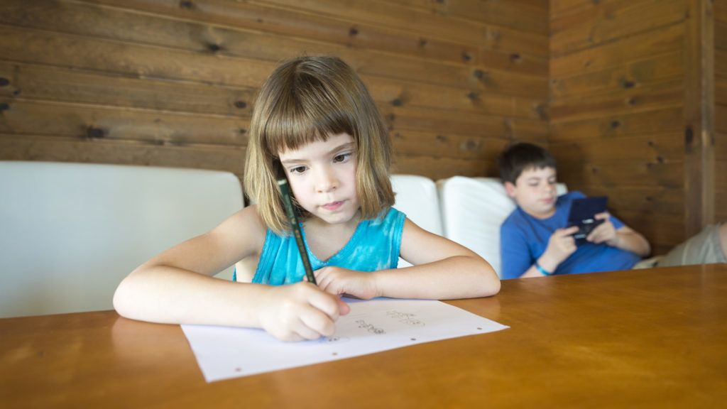 The girl draws while the child plays video games stretched on the sofa